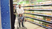 mercearia : Parents roll their daughter in the grocery cart in the supermarket. A happy family with a child is having fun in a supermarket, a little girl is sitting in a trolley and her parents are running.