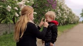 spor ayakkabısı : Portrait of mother and son on the background of flowering trees in the spring in the Park. Stok Video
