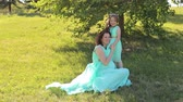 turkus : Happy pregnant mother with a little daughter in the same dress sitting on the grass in the Park, they laugh. Wideo