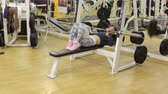 bicepsz : Sporty girl doing an exercise with a bar in the supine position in the gym. Bodybuilding. Stock mozgókép