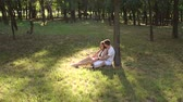 verificador : Young teen lovers are sitting on the grass leaning against a tree in the Park in Sunny warm weather. Wide shot. Slow motion. Stock Footage