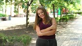 nagy : Girl model overweight with long flowing hair posing in a Sunny summer city Park. Fat young teen girl in the Park. Slow motion. Stock mozgókép