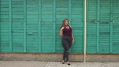 nagy : Portrait of a young girl overweight in the city Park on the background of a green wooden fence. Slow motion. Plus size model. Stock mozgókép