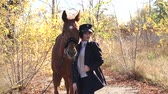 koňmo : Portrait of beautiful girl in special clothes and hat with brown horse in autumn. Young woman with her horse. Young professional model girl posing with horses and with a horse. Dostupné videozáznamy
