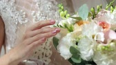 strumpfband : Close-up of the bride holding her wedding bouquet, she gently touches the flowers.