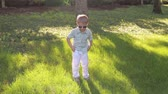 oblečený : A cute little boy in white trousers, a shirt and sunglasses stands on the green grass in the park and holds his hand over his glasses. Summer vacation. A little funny kid walks in a sunny park.