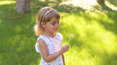 desejando : Happy child blowing dandelion flower outdoors. Girl having fun in spring park. Sunny portrait of cute little girl child blowing dandelion flower in summer day on the green grass.