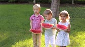 vodní meloun : Three cute little kids eating watermelon in a summer Sunny Park in hot weather. A large family with children on a picnic in the Park, they eat a ripe watermelon.
