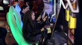 výhonky : A little girl with long curly hair plays video games in a modern childrens room. Modern shopping mall playground for kids and video games. Dostupné videozáznamy