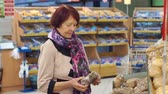 gastos : A senior woman of age buys bread at the supermarket. Grandmother of eighty years picks and buys bread at the grocery store. Slow motion.