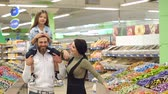dona de casa : Young fashionable parents buy sweets at the store, the daughter sits on the shoulders of her father. Portrait of a happy family in a supermarket. Slow motion.