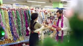 eğlenmek : Happy loving couple buying Christmas decorations and gifts for Christmas. The couple is having fun at the Christmas holidays in the supermarket. Slow motion. Stok Video