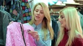 butik : Close-up of three beautiful young girls choosing clothes in the store, they are holding a pink jacket, joke and laugh. Portrait of three beautiful young women shopping in a clothes shop.
