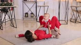 Тедди : Cute young mom playing with her little son lying on the floor of the house on a fluffy carpet.