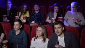 interessante : Group of teenager friends at the cinema watching a movie together and eating popcorn, entertainment and enjoyment concept. Young people sitting at the cinema.