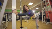 svaly : Girl doing exercise for legs on a press machine in the gym. A young athletic girl doing an exercise in a crossover in the gym among the many simulators.