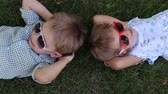 bratr : Two little funny child 4 years are in the summer on the grass and rest. The view from the top. Portrait of charming children in sunglasses on the grass.