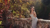 abandoned park : A luxurious, seductive girl in a very beautiful evening dress is leaning her back on a ruined stone balcony railing in an autumn abandoned park. Stock Footage