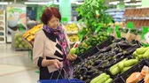 paketlenmiş : Close-up of a woman of eighty years buys zucchini in the supermarket. An elderly woman with wrinkles on her face chooses and buys products in the supermarket. Slow motion. Stok Video