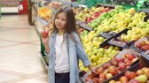 mercearia : Portrait of a little girl in a supermarket with an Apple in her hands on the background of shelves with fruit. Slow motion.