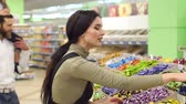 mercearia : Young fashion mother chooses sweets in the supermarket, the daughter sits on the shoulders of her father. Portrait of a happy family in a supermarket. Slow motion. Stock Footage