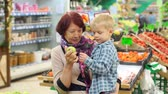 vnuk : An elderly woman with her little grandson buy fresh apples in a large supermarket. Grandmother and child make purchases at the grocery store.