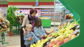 vnuk : Happy elderly woman with grandchildren in supermarket buys fruit. Portrait of grandmother of eighty years with her grandson and granddaughter in large modern supermarket buys of fruits and vegetables.