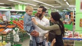 nákupní vozík : Portrait of a big happy family in the supermarket, they stand on the background of fruits and vegetables. Shopping, food, sale, consumerism and people concept. Slow motion. Dostupné videozáznamy