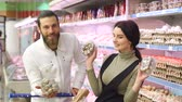 codorna : Young happy couple choose quail eggs in supermarket. Young family buying eggs at the grocery store. Slow motion. Portrait.