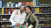 expressando positividade : Portrait of a young fashion couple in a supermarket or in a wine shop with a full cart of products. Bearded man with his wife in a liquor store, portrait. Slow motion. Choosing wine for dinner.