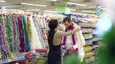eğlenmek : Happy loving couple buying Christmas decorations and gifts for Christmas. The girl puts a garland on her boyfriends head, the couple is having fun at the Christmas holidays in the supermarket.Slow mo