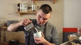 barista : Professional barista pouring steamed milk into coffee cup making latte art. Close-up of hands pouring the warm milk in coffee cup. The barista is making cappuccino. Slow motion.