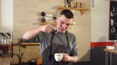 milk pouring : Barista poured into a Cup of coffee cinnamon, cocoa or chocolate, the process of making aromatic coffee and cappuccino in the coffee shop. Slow motion. Stock Footage