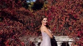 clivagem : A beautiful girl in a long silver evening dress walks in an old abandoned park in the autumn, she stands on a ruined stone staircase that winds wild grapes with red leaves. Wide shot.