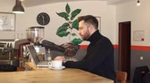 личность : Portrait of a young bearded man businessman in a coffee shop, he works on a laptop sitting at the bar and drinks a fragrant cappuccino. Slow motion. Стоковые видеозаписи
