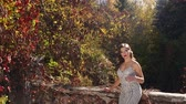 clivagem : A beautiful girl in a long silver evening dress walks in an old abandoned park in the autumn, she stands on a ruined stone staircase that winds wild grapes with red leaves.