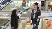 seçen : Fashionable young girl with younger sister walking in the Mall. A young girl with a younger sister are in a bright modern shopping center on the background of escalators.