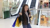 sacco regali : Portrait of a cute little girl with long curly hair in a shopping center with packages against the background of an escalator, she lays the bags on her shoulder and shows her thumb up.
