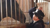vaquera : Young seductive girl with professional make-up in the village stable near the brown horse. Model posing in the stable on a horse farm. Slow motion.