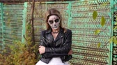 lidércnyomás : A young girl with a creepy make-up in the form of a skull on her face in a wedding dress and a leather jacket on the background of an old rusty fence. Halloween. The image of the dead bride.