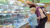 unokája : An old grandmother with a small grandson in the supermarket choose sweets on the counter. Portrait of an elderly woman with a child in the supermarket. A grandmother with a grandson to buy a cake.