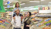 corredor : Young fashionable parents buy sweets at the store, the daughter sits on the shoulders of her father. Portrait of a happy family in a supermarket. Slow motion.