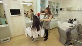 cabeleireiro : Hair stylist work on woman hairstyle in salon. Drying long brown hair with hair dryer and round brush. Close-up.