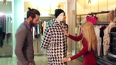 sleva : The couple is shopping at a clothing store, they look at the coat on the mannequin. The girl wants to buy a coat and her husband is against.