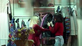 tentação : Two young fashionable women, a blonde and a brunette, choose clothes in a fashionable clothing store, they try on autumn and winter coats. Stock Footage
