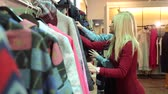 tentar : Two girlfriends are joking while do shopping at the store. Two smiling woman shopping in retail store. Portrait of two beautiful young women shopping in a clothes shop. Stock Footage