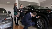 A young successful man with two girls chooses a new car in the showroom, he looks carefully at the wheels. Choosing and buying a new car. Archivo de Video
