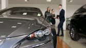 The image of the car in the showroom, in the background a man the seller advises two young girls when choosing a new car. Blurred background. Silhouette of people in the showroom.
