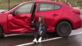 Scared teen girl sitting on the wet ground near the broken car, she got into a car accident, crying and holding her head. Stockvideo