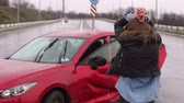 A young girl in a leather jacket got into a car accident, she is upset walking around the broken car and waiting for help. Car accident on the road in the rain. Stockvideo